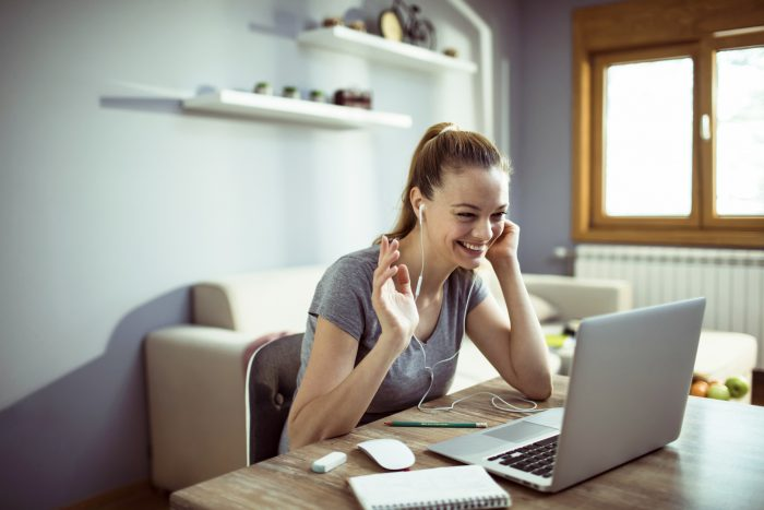 Close up of a young woman using a laptop for teleconferencing at home